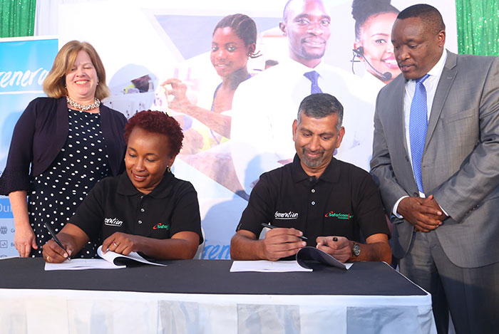 Safaricom Foundation's Sylvia Mwangi and Generation Kenya's Ramakrishnan Hariharan sign the partnership agreement as USAID's Heather Schildge and the Principal Secretary in the State Department of Post Training and Skills Development, Mr. Alfred Cheruiyot, look on